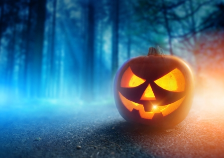 A glowing Jack O Lantern in adark mist Forest on Halloween
