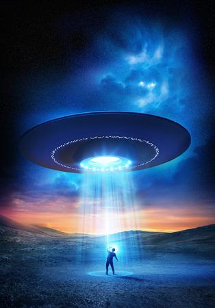 Foto de Out There. A man shields his eyes from the bright UFO above him. Abduction probable! - Imagen libre de derechos