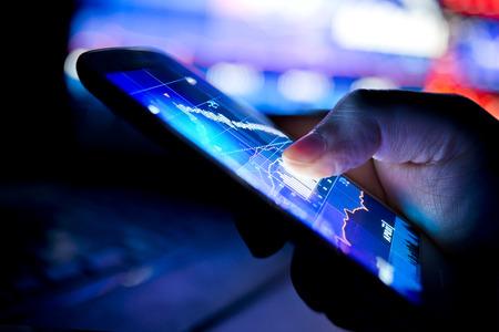 Photo pour A city businessman using a mobile device to check stocks and market data. Close up shot. - image libre de droit
