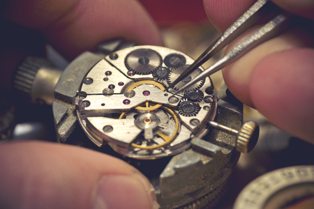 Photo pour Working On A Mechanical Watch. A watch makers work top. The inside workings of a vintage mechanical watch. - image libre de droit