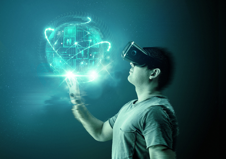Photo pour A young man wearing virtual reality (VR) goggles and headset with a projection of a digital world. - image libre de droit
