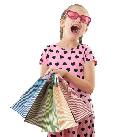 Photo for pretty little girl yawns with shopping bag, studio portrait, dressed in pink with heart shapes, white background - Royalty Free Image