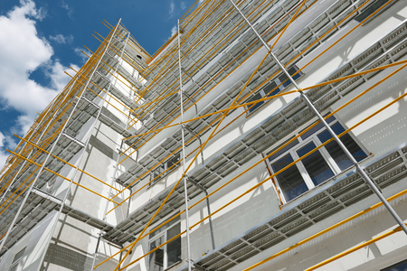 Photo pour scaffolding near a new house, building exterior, construction and repair industry, white wall and window, yellow pipe - image libre de droit