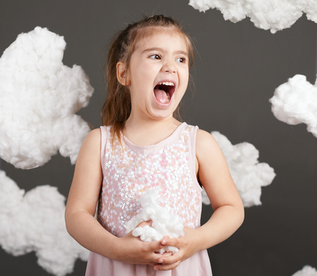 Photo for girl playing with clouds, shot in the studio on a gray background - Royalty Free Image