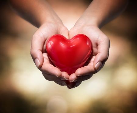 Foto de heart in heart hands- warm background  - Imagen libre de derechos