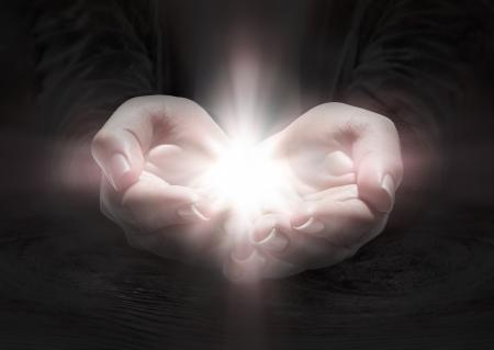 Foto de light in hands - pray the crucifix in darkness  - Imagen libre de derechos