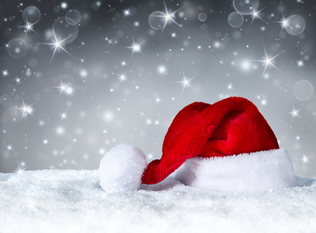 Foto de Santa Claus hat with snow and silver snowfall background - Imagen libre de derechos