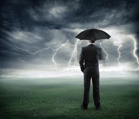 Foto de risk and crisis  businessman below storm with umbrella - Imagen libre de derechos