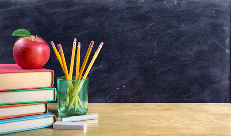 Foto de apple on books with pencils and empty blackboard - back to school - Imagen libre de derechos