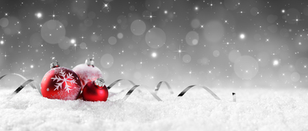 Photo pour Red Baubles On Snow With Sparkling Stars On Silver Background - image libre de droit