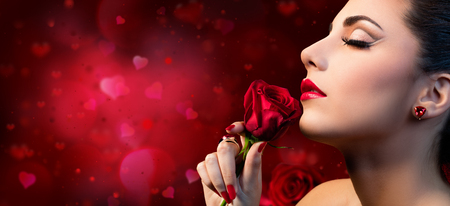 Foto de Valentines Beauty - Sensual Model Woman Touching Red Rose Flower - Imagen libre de derechos
