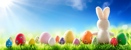 Photo for Bunny With Decorated Eggs On Sunny Meadow - Spring And Easter Background - Royalty Free Image