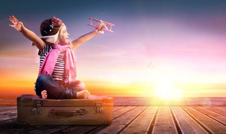 Foto de Dream journey - Little Girl On Vintage Suitcase At Sunset - Imagen libre de derechos