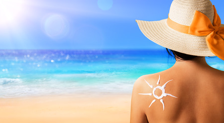 Foto de Woman With Suntan Lotion Shaped Sun - Imagen libre de derechos