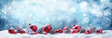 Photo pour Snowy Christmas Balls And Pinecones In Wintery Scene - image libre de droit