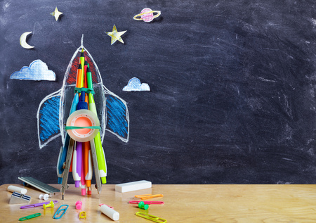 Photo for Startup - Rocket Drawing With School Supplies On Table - Royalty Free Image