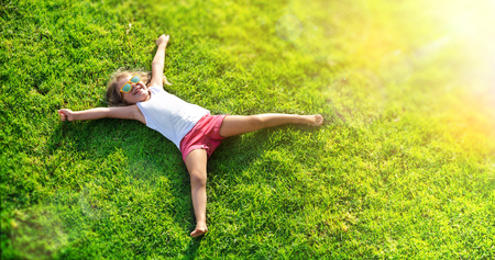 Foto de Smiling Little Girl Lying On Grass Meadow - Imagen libre de derechos