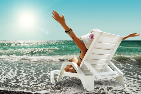 Happy woman in chaise lounge on the sea beach in sunny day