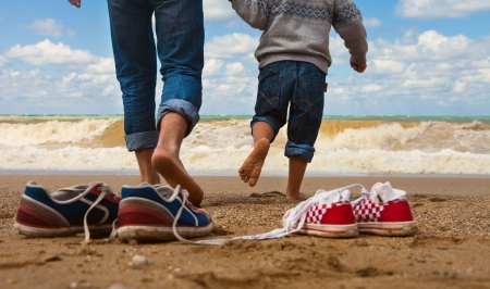 Photo for Close up image father and son legs walk at the seaside - Royalty Free Image