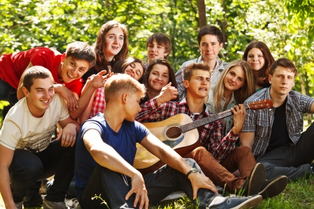 Group of young people singing by guitarin summer park