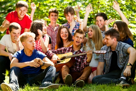 Photo for Ggroup of young people singing in unison by guitar - Royalty Free Image
