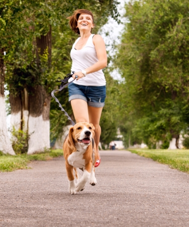 Photo for Happy young woman jogging with her beagle dog - Royalty Free Image