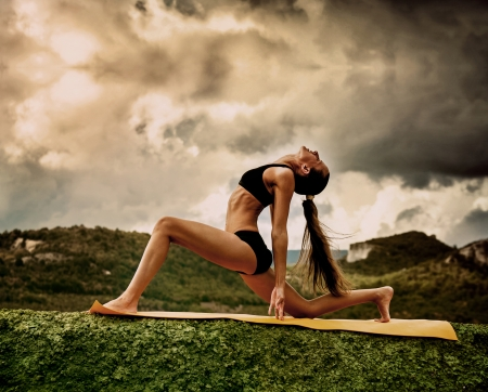 Foto de Slim young woman makes warrior yoga pose  - Imagen libre de derechos