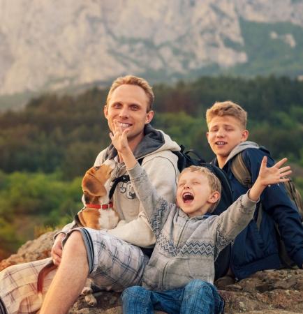 Foto de Happy family on mountain walk  Father with sons and pet - Imagen libre de derechos