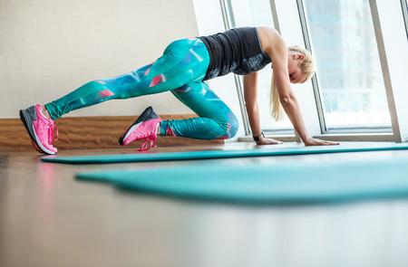 Foto de Beautiful blonde female doing fitness exercises in modern gym - Imagen libre de derechos
