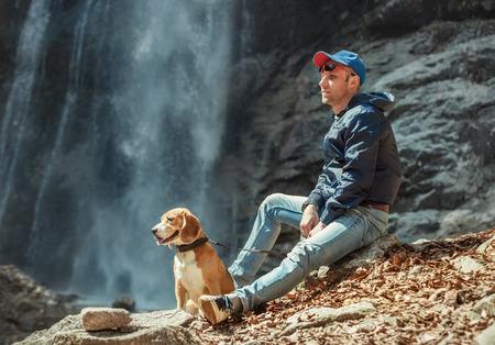 Photo pour Man with dog sitting near waterfall - image libre de droit