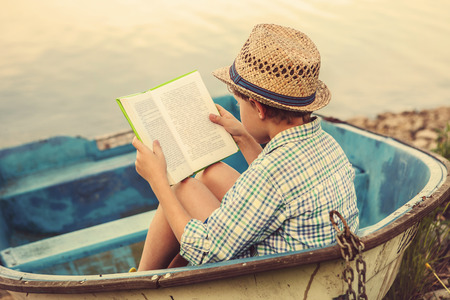 Photo pour Reading boy in old boat - image libre de droit