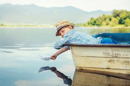 Photo for Little boy launch paper ship lying in old boat - Royalty Free Image
