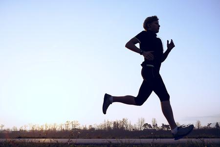 Photo pour Silhouette runner in sunset rise - image libre de droit