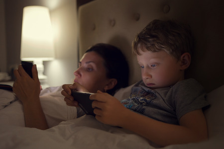 Photo pour Mother with son lying in bed and look in their electronic device - image libre de droit
