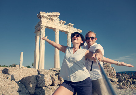 Foto de Happy young couple take a selfie photo on antique ruins. Temple of Apollo, Side, Turkey - Imagen libre de derechos