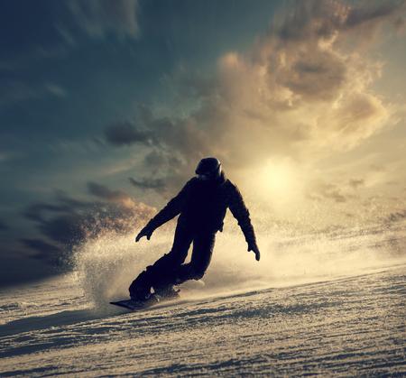 Foto de Snowboarder slides down the snowy hill - Imagen libre de derechos