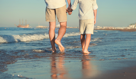 Photo for Father and son legs on the sea surfline close up image - Royalty Free Image