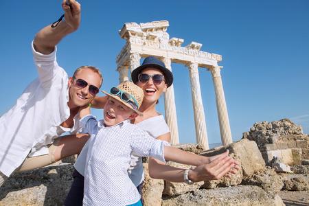 Foto de Positive young family take a sammer vacation selfie photo on antique sights view - Imagen libre de derechos