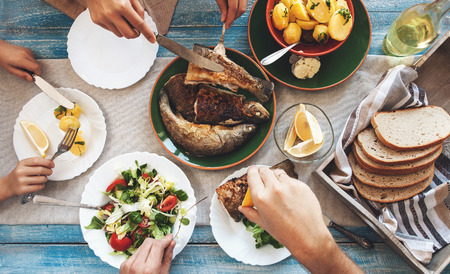 Photo pour Family dinner with fried fish, potato and salad - image libre de droit