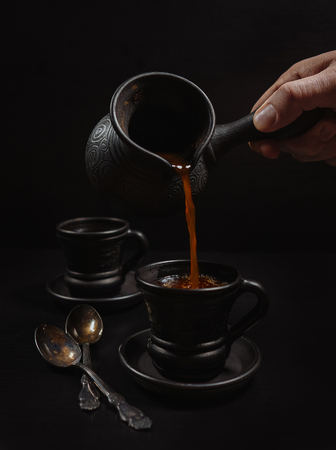 Photo pour Men hand pouring the coffee in clay cup: black on the black - image libre de droit