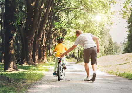 Photo pour Father help his son ride a bicycle - image libre de droit