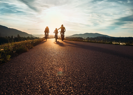 Foto de Ð¡yclists family traveling on the road at sunset - Imagen libre de derechos