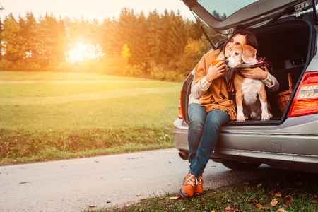 Photo pour Woman with dog sits in car trunk on autumn road - image libre de droit