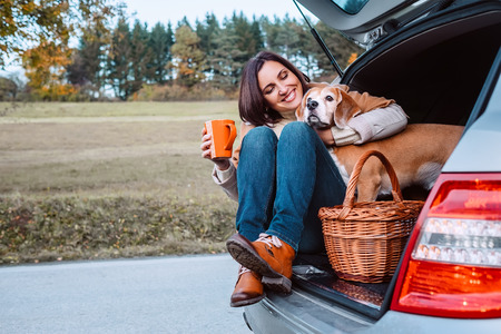 Photo pour Woman with her dog have a tea time during their autumn auto travel - image libre de droit