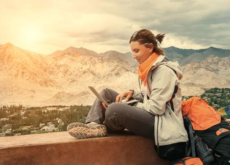 Foto de Backpacker with laptop sits on the top view point under mountain settelment - Imagen libre de derechos
