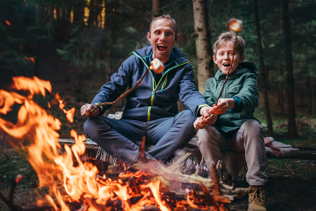 Photo for Father and son overroast their marshmallow candies on the campfire - Royalty Free Image