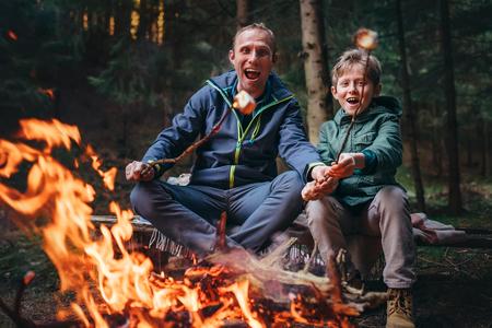 Foto de Father and son overroast their marshmallow candies on the campfire - Imagen libre de derechos