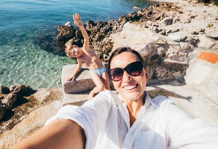Foto de Mother with son take vacation selfie photo in Adriatic Sea Bay - Imagen libre de derechos