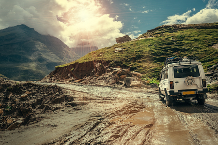 Foto de Off-road vehicle goes on the mountain way during the rainy season - Imagen libre de derechos