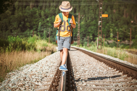 Foto de Little boy with backpack walks on railway track - Imagen libre de derechos